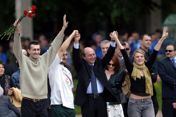 Former hostages Sorin Miscoci (L) and Ovidiu Ohanesian, Romanian President Traian Basescu and former hostage Marie-Jeane Ion (R) raise their hands 23 May 2005 at Bucharest military airport upon the arrival from Iraq of the three journalists, who were released 22 May after 55 days in captivity. AFP PHOTO DANIEL MIHAILESCU